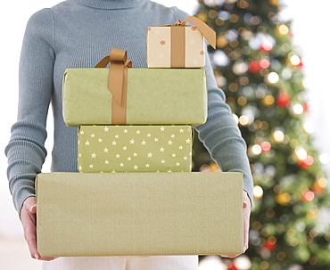 Woman holding stack of Christmas gifts