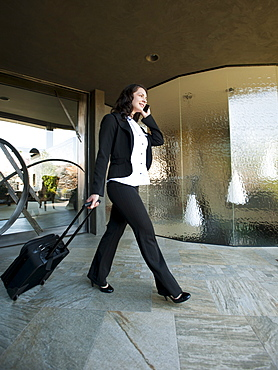 Woman leaving house with piece of luggage, USA, Utah, St George