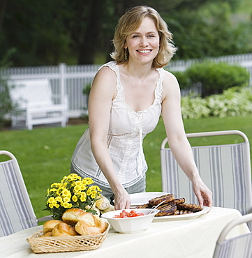 Woman setting table outdoors