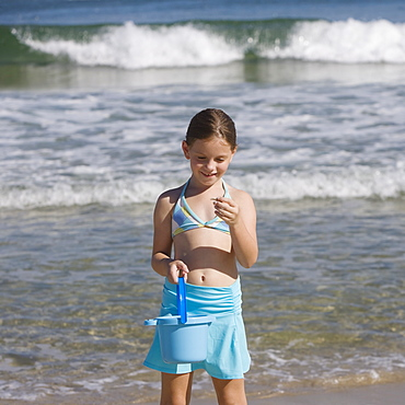 Girl looking at shell at beach