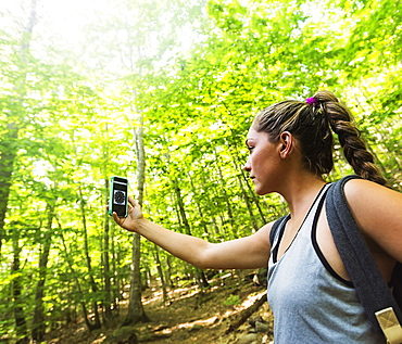 Female hiker looking at compass on phone