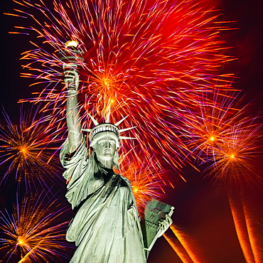 Firework display behind Statue of Liberty