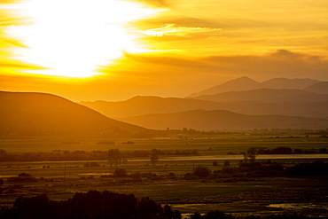 Rural landscape by hills at sunset in Picabo, Idaho, USA