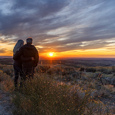Couple in field at sunset at Boise Foothills in Boise, Idaho, United States of America
