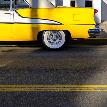 Yellow old fashioned car on road