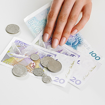 Close up studio shot of woman's hand and money