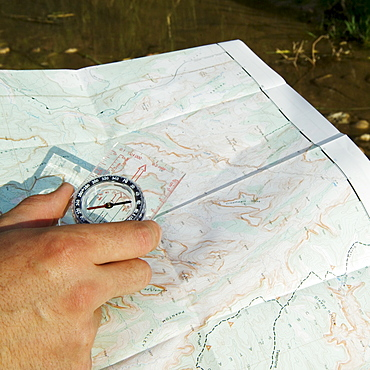 Hand holding a compass and map