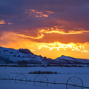 Snowy mountains under dramatic sky at sunrise