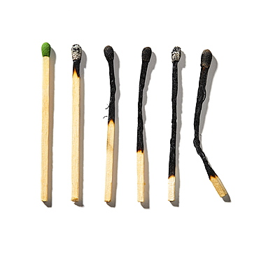 Row of burnt matchsticks on white background