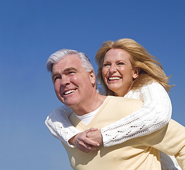 Senior man giving senior woman piggy back ride outdoors