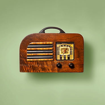 Retro wooden radio on green background