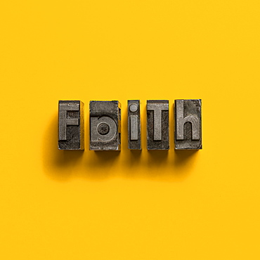 Wooden printer font letters spelling word Faith