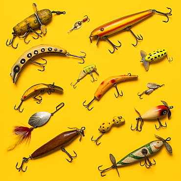 Arranged group of vintage fishing lures on yellow background