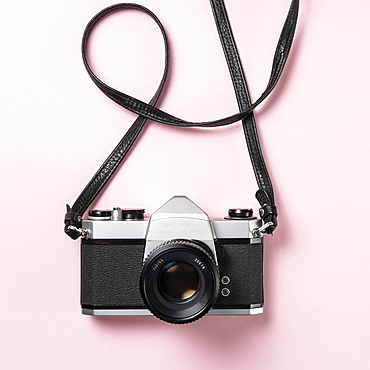Vintage SLR camera on pink background