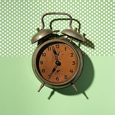 Vintage alarm clock on green background