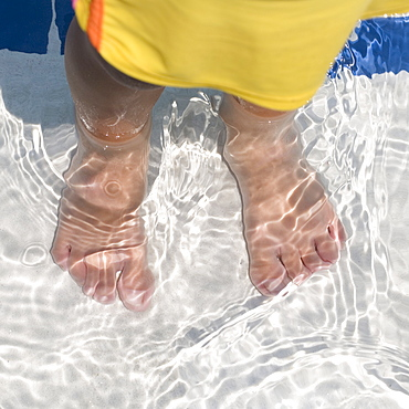 Child's feet standing in water