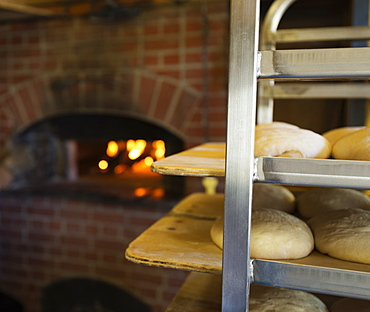 Artisan bread on shelves in kitchen with brick oven