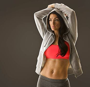 Studio portrait of woman in sports bra and hooded shirt