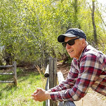 Senior farmer leaning on wooden fence near Sun Valley