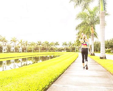 Woman walking along promenade drinking water, Jupiter, Florida