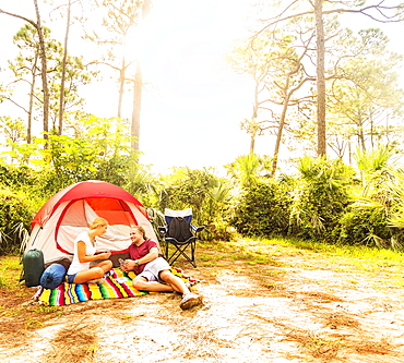 Couple playing cards in front of tent, Tequesta, Florida