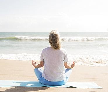 Senior woman practicing yoga on beach, Jupiter, Florida
