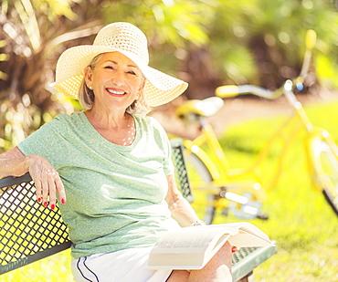 Portrait of senior woman reading book in park