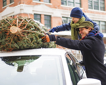 Man with kid (6-7) bonding Christmas tree, Jersey City, New Jersey, USA