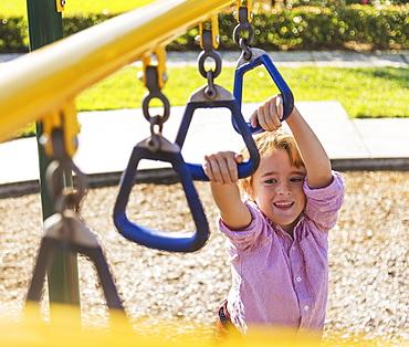 Boy (8-9) playing on playground, Jupiter, Florida, USA
