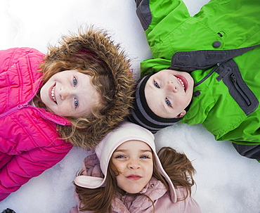 Directly above portrait of three children (2-3, 4-5) lying on snow