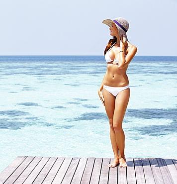 Young woman in bikini standing on jetty