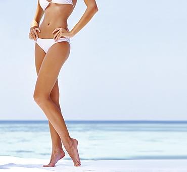 Young woman wearing bikini, low section