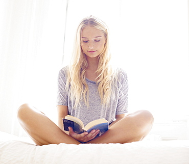 Teen (16-17) girl reading on bed