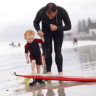 Father and his son (2-3) on beach by surfboard