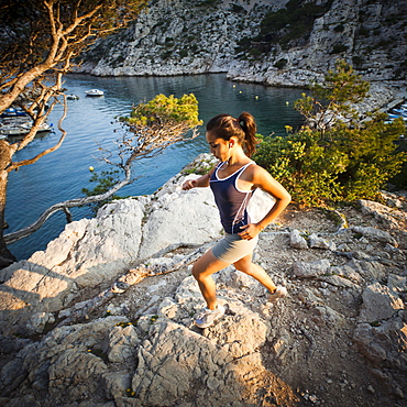 France, Marseille, Young woman jogging in rocky terrain, France, Marseille
