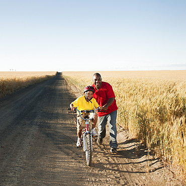 Father teaching son (8-9) how to cycle on along dirt road