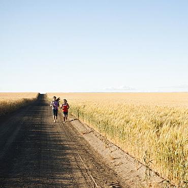Girls (12-13, 10-11) running along dirt road