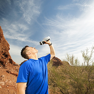 USA, Arizona, Phoenix, Man pouring water on his face