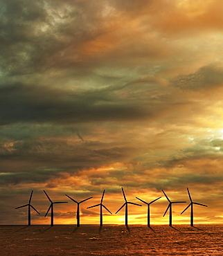 Wind turbines in sea at sunset