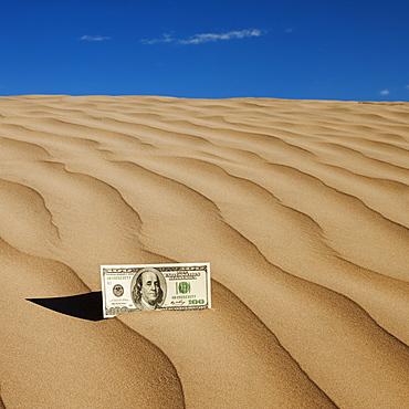 100 dollar bill on sand in desert