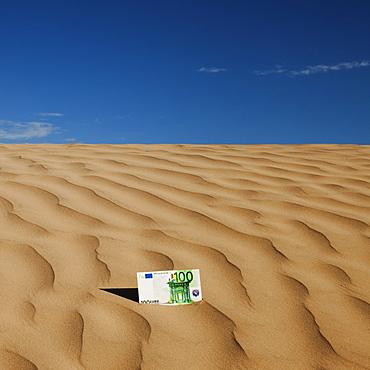 100 euro bill on sand in desert