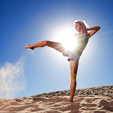 Female dancer kicking her leg on the beach