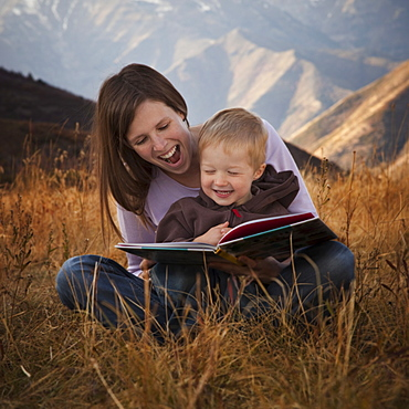 Mother and son reading outdoors