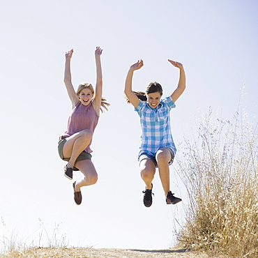 Young female friends jumping