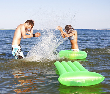 Young couple splashing in ocean