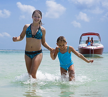 Sisters running through water, Florida, United States