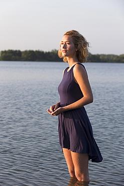 Beautiful woman standing in lake, Netherlands, Gelderland, De Rijkerswoerdse Plassen