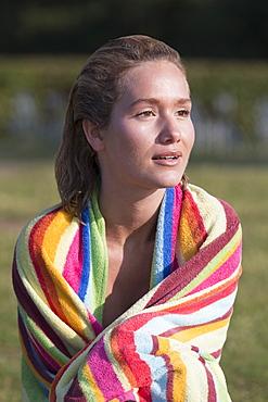 Woman wrapped in stripped towel, Netherlands, Gelderland, De Rijkerswoerdse Plassen