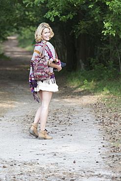 Woman walking dirt road, Netherlands, Gelderland, Hatertse Vennen