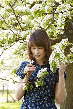 Portrait of young woman in blooming orchard